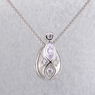 "You will feel captivated by the feel of modern and vintage in this elegant diamond pendant. 14 karat white gold with .16 carats of sparkling ideal cut diamonds. This beautiful diamond pendant measures 1/2 inch long, and dangles on a 14 karat white gold 1.1mm wheat chain, 18"" long.  Designed and created in our studio by the artist Stuart J."
