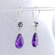 "We picked these beautiful Zambian Amethyst drops because the color was so rich! We added beautiful light Blue Topaz for a perfect match. Handmade in 14 karat white gold, with blue topaz buff top gems set in bezels, and the amazing deep purple amethyst drops, making these earrings the perfect accessory to any outfit! These drop dangle earrings measure 1 1/4"" long, and hang on 14 karat white gold wires.  Designed and created in our studio, by the artist Stuart J. Adelman."