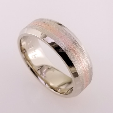 We custom make all our rings, one at a time. So if you can think it, we can make it. Here is a version of a simple and timeless man's wedding band that will last a lifetime. We crafted it in 14 karat white gold, 8mm wide, with a 2mm wide 14 karat rose gold center. A perfect match to the brides rose and white gold halo engagement ring! Call us for more information about how we can make this design just for you, or keep it as it is, and enjoy it's beauty!  Designed and created in our studio, by the artist Stuart J. Adelman.