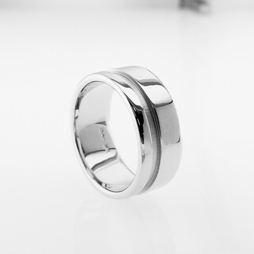 How great it is to feel a nice hearty ring on your finger! One that is made to last forever! This is the philosophy we have for making jewelry. Created in solid 14 Karat white gold, measuring 10mm wide, with a beveled edge to give this ring style. We make a ring that will be passed down from generation to generation. That will make you proud, and us happy!   And, of course, we can custom make this any way you like, including with diamonds or...  Designed and created in our studio, by the artist Stuart J. Adelman.