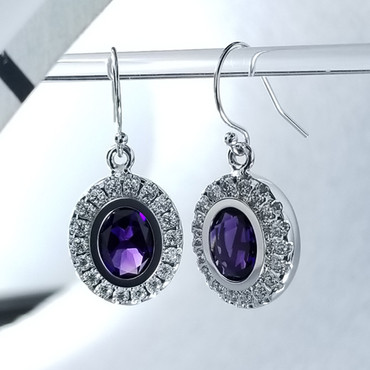 """We created these timeless Amethyst and diamond halo earrings with a modern flare. There are no prongs to worry about, and our special setting style makes the 3/4 carat of super sparkly, Ideal cut diamonds look like twice the amount. Handmade in 14 karat White gold, two 9mm by 7mm oval, bezel set, deep purple amethysts create enough drama for evening, but not too much for every day wear. Dangling on handmade white gold wires, they measure about 1"""" long, and are designed and handcrafted by the artist, Stuart J. Adelman.  Call us for more information about how we can customize this design Just For You."""