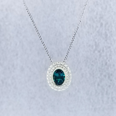 """We created this timeless Chatham Created Emerald and diamond halo pendant with a modern flare. There are no prongs to worry about, and our special setting style makes the .17carat of super sparkly, Ideal cut diamonds look like twice the amount. Handmade in 14 karat Green gold, one 1.14 carat oval, bezel set, deep green emerald create enough drama for evening, but not too much for every day wear. Hanging on a .07mm Wheat Chain 18"""" White Gold, it measures about 1/2"""" long, and is designed and handcrafted by the artist, Stuart J.   Call us for more information about how we can customize this design Just For You."""