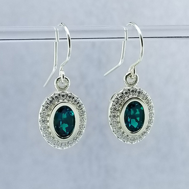 """We created these timeless Emerald and diamond halo earrings with a modern flare. There are no prongs to worry about, and our special setting style makes the 1/3 carat of super sparkly, Ideal cut diamonds look like twice the amount. Handmade in 14 karat Green gold, two 7x5 oval, bezel set, deep green created emeralds create enough drama for evening, but not too much for every day wear. Dangling on handmade white gold wires, they measure about 1/2"""" long, and are designed and handcrafted by the artist, Stuart J. Adelman.  Call us for more information about how we can customize this design Just For You."""