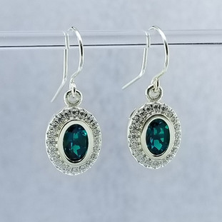 "We created these timeless Emerald and diamond halo earrings with a modern flare. There are no prongs to worry about, and our special setting style makes the 1/3 carat of super sparkly, Ideal cut diamonds look like twice the amount. Handmade in 14 karat Green gold, two 7x5 oval, bezel set, deep green created emeralds create enough drama for evening, but not too much for every day wear. Dangling on handmade white gold wires, they measure about 1/2"" long, and are designed and handcrafted by the artist, Stuart J. Adelman.  Call us for more information about how we can customize this design Just For You."