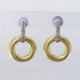 Inspired by natural colors and shapes, these sophisticated diamond circle earrings are crafted in rich 18 karat yellow gold, with 18 karat white gold tops, set with .11ct ct. total weight of sparkling diamonds. Hanging on 18 karat white gold posts. These earrings are truly a knock out piece. Measures 3/4 inches long. Exceptional in every way, and designed by the acclaimed jeweler Aaron Henry, in his California studio.
