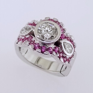 Wed- 403-  Custom designed ring for our customer's 35th wedding anniversary, using her moms center diamond. We added these sparkly diamonds and vibrant pink sapphires to make this ring perfect!