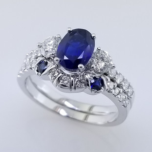 Wed- 399-  We custom designed this wedding band to go with our customers engagement ring.  Created in white gold, setting 2- matching round sapphires, and many sparkly diamonds to make this wedding set complete.