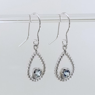 You will be captivated by this mix of modern and vintage in these sweet and sassy dangle earrings.  Handmade in 14 Karat white gold, with these dreamy pale blue buff top blue topaz gemstones. You will have so much fun wearing them day or night.  Measures 1 inch long and hangs on 14 karat white gold wires.