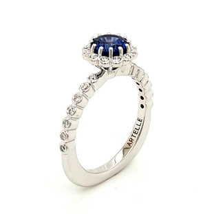 This sweet and delicate halo engagement ring was custom designed for that special person. Created in 14 karat white gold, set with .20ct. T.W. of our perfectly cut and very sparkly lab grown diamonds, and the center set like a delicate flower, holding a 1.17ct. round Chatham(r) lab created, dreamy blue sapphire gemstone. So simple, but so beautiful! Designed and created in our studio by the artist, Stuart J. Call us to find out how we can make this gorgeous ring any way you like!