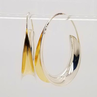Jewelry to soothe and flow, our Zen earrings are the perfect oval hoop earring with a twist. Hand-forged silver and 18 Karat yellow gold. Elegant, casual, and comfortable with a modern flare.  These amazing hoop earrings stand 2 inches tall.