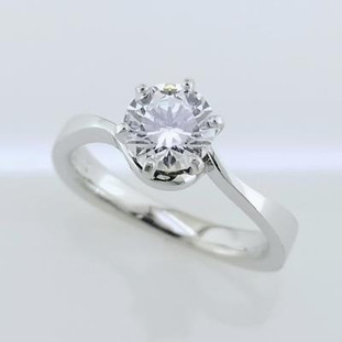 This solitaire diamond engagement ring is timeless, but with a modern twist. Shown in 14 karat white gold, with a 1ct. round diamond (sold separately), this ring will set off that sparkly diamond beautifully. We can make this in any color of gold, or platinum, and with any size diamond, ours or yours. Designed, and created in our studio by the artist, Stuart J.