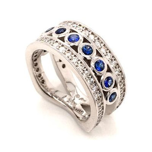 With this spectacular diamond and blue sapphire anniversary ring on your finger, you will feel like royalty, and be the envy of all of your friends. With .75 carats of Ideal cut diamonds, round diamonds cascading down the outside edges, and beautiful blue sapphire round cuts down the center, Sparkle is this rings middle name. There are no prongs to catch, and it is very comfortable to wear. Made with a mix of round diamonds and round cut blue sapphires, it is a feeling of traditional with a modern flare. This custom designed diamond anniversary ring is individually crafted to be Perfectly You. Call us for more information about how we can customize this design Just For You.   Designed, and created in our studio by the artist Stuart J.  This diamond anniversary ring is priced in 14k gold, and can be made in any karat or color, and in platinum. Makes a great anniversary gift for 10, 20, 30 or more years together.