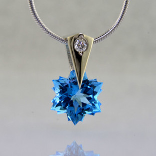 The hottest snowflake around! Custom cut, exclusively for us, in Canada. Dangling from a 14 karat white gold Piercette® pendant, with a perfectly cut sparkling 8mm Blue Topaz snowflake cut gemstone, and accented with a single .03ct. Ideal cut Diamond. Includes a 14k white gold 1.1mm diameter,wheat chain, 18inches long. Measures 1/2 inch long.  Designed and handmade by the artist Stuart J.  A Piercette® is a patented method of setting, with a gemstone that moves. The gem is set so that it swivels with every movement of the wearer, exhibiting extra sparkle.
