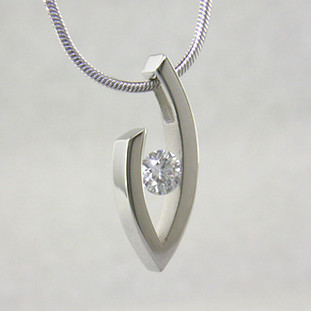 Simple elegance describes this pendant, which shows off a single Diamond to perfection. We can make this piece for any size Diamond and in most shapes - including marquise, pear and oval. Crafted in 14 karat White Gold, this one measures about 1 inch and holds a 0.81ct. F color, VS-2 clarity Diamond, elegantly displayed on a 14 karat White Gold 1.2mm round omega wire necklace, 16 inches long.  Got an extra diamond sitting in a drawer? We know what to do with it.  Designed, and created in our studio by the artist Stuart J.