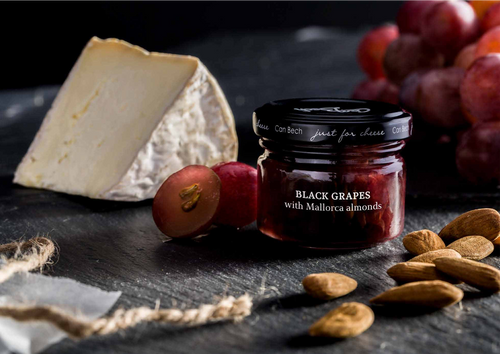 •Black grapes with Mallorca almonds •Just for Cheese •For pairing with soft paste and washed rind cheeses •Produced in Barcelona, Spain •2.57 oz  73 g  Black Grapes. Picked at its peak, this slightly watery texture and sweet taste combine with strong nature of almonds to pair with washed rind cheese.