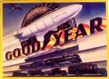 GOODYEAR EMBOSSED SIGN  HAS A HUGE TIRE, IN FRONT OF THE TIRE IS THE GOODYEAR BLIMP, SHIP, TRAIN AND OLD TIME CARS, TURCKS AND BUS. (SINCE WHEN DID TRAINS, BLIMPS AND SHIPS USE TIRES?)