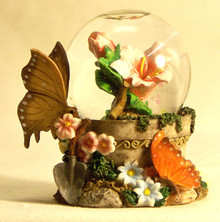 """MINITURE SNOW GLOBE WITH BUTTERFLYS & FLOWER  MEASURES 2 1/2"""" X 2"""" X 3 1/8"""""""