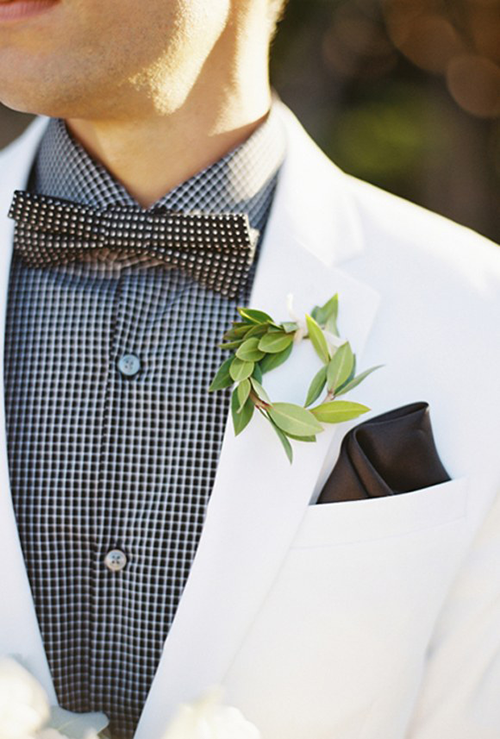 White grooms suit with black and white checkered shirt and bow tie