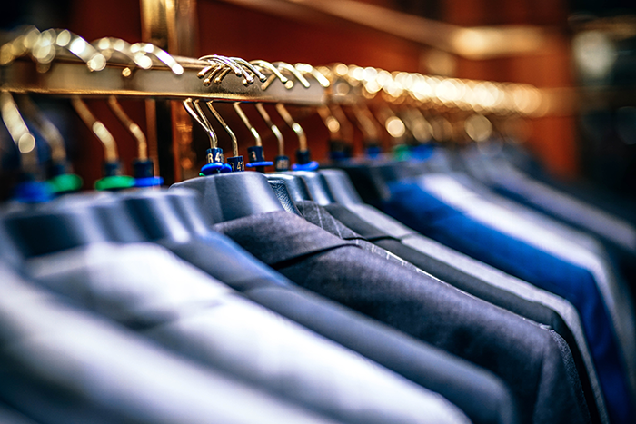 suits on a rack at a typical menswear store