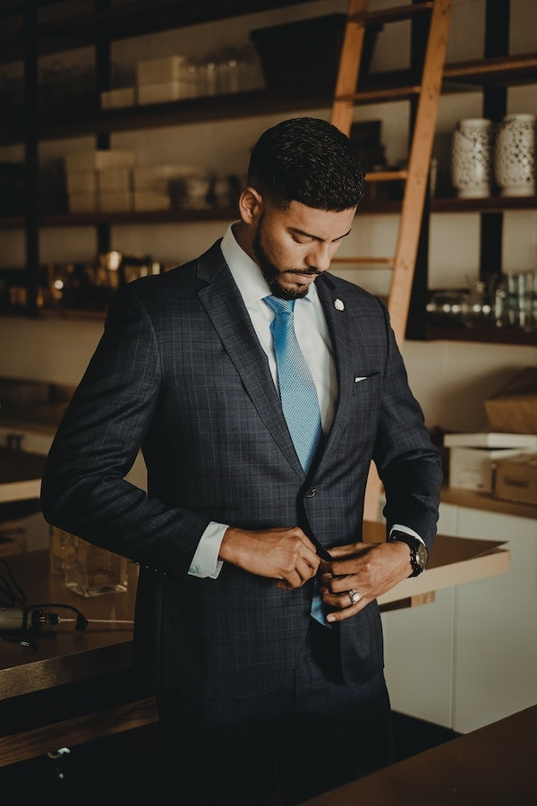 man buttoning suit jacket