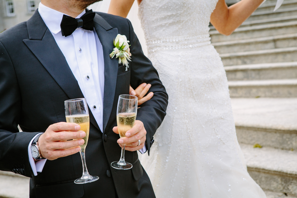 a groom wearing a black tuxedo at a wedding