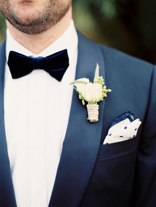 Groom wearing a midnight blue velvet bow tie