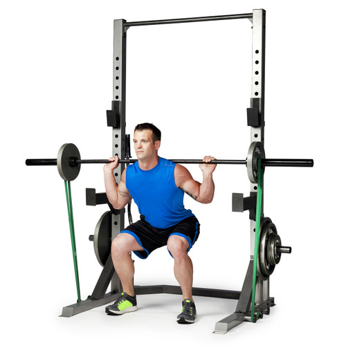Model squatting with barbell and resistance bands attached to CAP Deluxe Power Rack