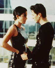 This is an image of 243084 Keanu Reeves & Carrie-Ann Moss Photograph & Poster
