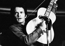 Merle Haggard holds up his guitar whilst playing it 5x7 inch photo