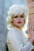 Jayne Mansfield stands next to brick wall in grey jacket 8x10 photo