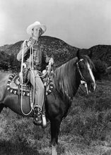 Gene Autry western great riding his horse holding lassoo 5x7 inch photo