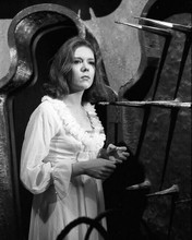 Diana Rigg wearing nightdress & robe looks at spears on wall Avengers 8x10 photo