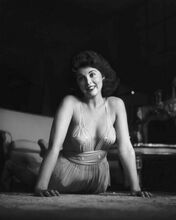 Tina Louise in low cut dress poses on floor smiling 8x10 inch photo
