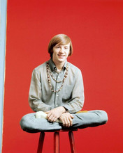 The Monkees Peter Tork wears beads around neck sitting on stool 8x10 inch photo