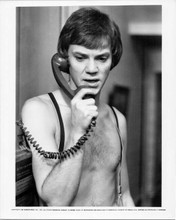 Malcolm McDowall 1972 8x10 inch original photo bare chested on telephone
