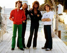 The Bee Gees brothers Barry Robin Maurice & Andy pose on boat dock 8x10 photo