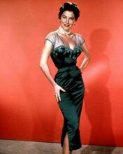 Ava Gardner glamour pose in low cut dress hands on hips 8x10 inch photo