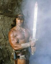 Arnold Schwarzenegger holds the gleaming sword as Conan The Barbarian 8x10 photo