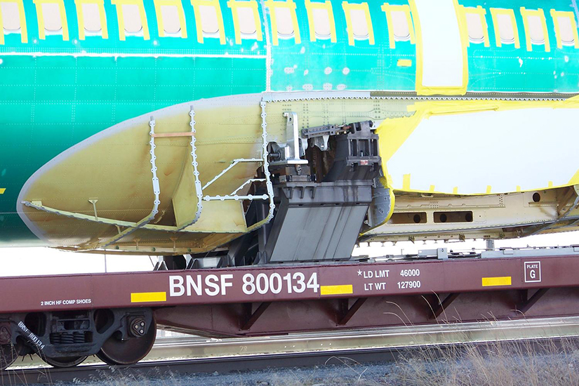 737 Fuselage Attached to BNSF 800134 Flatcar with Anti-Corrosive Primer, Plastic Film, and Tape Applied