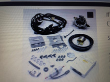 Description – This kit does not have a California E.O. # (exemption order)  – In the state of California this kit can be installed on 1975 or earlier vehicles only  For converting an I6, V6 or V8 engine from carburetor to throttle body fuel injection. Uses remanufactured GM throttle body appropriate for engine size. Operates GM engines with or without ECM controlled ignition. Very popular for older street-driven vehicles or 4 wheel drive vehicles. Contains all sensors, components, wiring harnesses, ECM and fuel pump to install fuel injection on your engine. Custom calibration PROM for your engine. ECM installs under dash. Fuel pump installs in main fuel line, and bypass fuel is returned to the tank. Harness includes diagnostic connector, and diagnostic is similar to 1986-92 GM pickup.