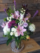 A tall and full fountain style arrangement with seasonal classic garden flowers