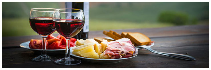 Still life red wine, cheese and prosciutto. Romantic dinner outdoors.