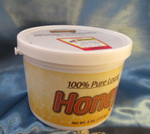 A 4 pound plastic tub of Monastery Honey
