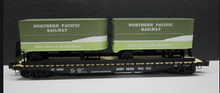 Lionel  NP  twin pup  trailers on  50'  wood deck flat car
