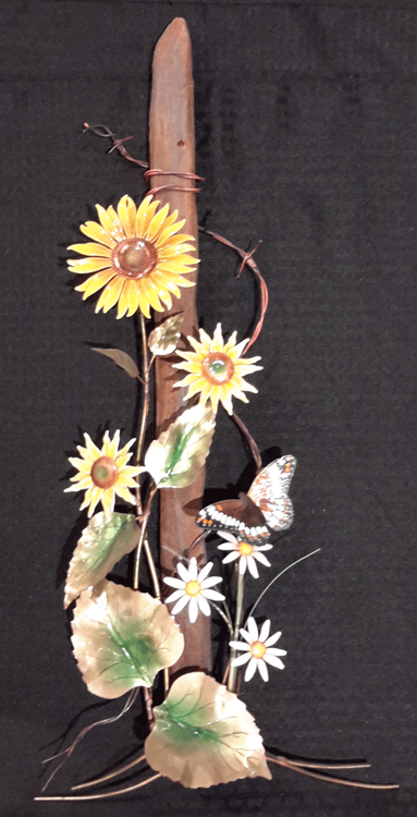 """Wildflowers with Barbed Wire Fence 13""""w x 28""""h  The sculpture is hand made using vitreous enamel (powdered glass) layered over solid copper and then kiln fired to fuse the glass to the metal."""