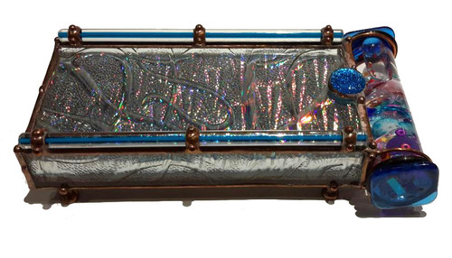 """This Kaleidoscope by Sue Rioux designs is called Symphony. Exterior details included long blue glass rods along the top edges and a shimmery dichroic glass accent bead nestled on the top. All the soldering has a copper colored patina, decorative copper beads and little feet are added to the bottom. This Kaleidoscope is 7.5"""" x 4"""" x 1 7/8"""" .   Please call to confirm availability and to purchase. 970-586-2151"""