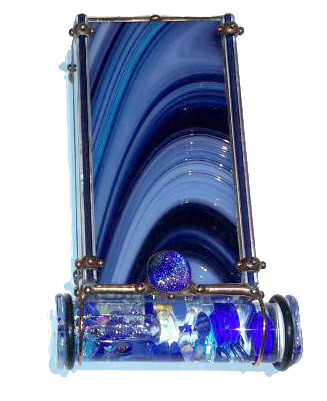 "The MIDNIGHT BLUE kaleidoscope by Sue Rioux designs is 6"" x 3"" x 1"". The oil filled glass cell is easy to turn with its rounded edge square glass knobs. The cell holds bits of iridescent dichroic glass pieces, beads, wire and small baubles in many shades of blues from dramatic cobalt and navy to light aqua and sea blues.  Please call to confirm availability and to purchase. 970-586-2151"