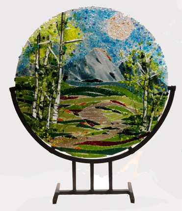 "The 'Spring Ribbons'  in a steel stand by Kathi D. Dougherty captures the spring colors of a lovely mountain day. This 16"" fused glass round rests in a black coated steel stand for displaying.  Shop now or call to speak with a sales associate for additional assistance.   Earthwood Collections, 970.586.2151"
