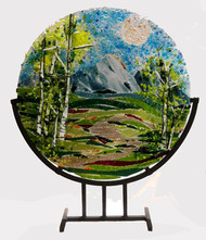 """The 'Spring Ribbons'  in a steel stand by Kathi D. Dougherty captures the spring colors of a lovely mountain day. This 16"""" fused glass round rests in a black coated steel stand for displaying.  Shop now or call to speak with a sales associate for additional assistance.   Earthwood Collections, 970.586.2151"""