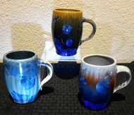 """This Bistro Mug is made by Campbell Pottery. The mug is 4 1/2"""" x 5"""" wide and holds 11oz. It is available in Cream/Green/Blue or New Glaze, dark and Light Stellar glaze.  Each porcelain form is hand glazed and crystals grow in the firing process so colors and patterns will vary."""